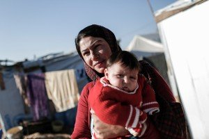"Shereen Sabah, 34, a mother of three, holds her 2 month old daughter Alaa outside the tent in which she now lives in an IDP camp outside Erbil, Iraq, on December 4 2014. Shereen, and family, who are Iraqi Shabak people from the Sinjar area of northern Iraq, came to Erbil in August, after Islamic State militants overran their town. The so-called Islamic State is a radical Islamic militant group that controls territory in both Iraq and Syria. Thousands of Yazidis and other minorities fled from their advance in neighbouring provinces to Erbil. She has been registered to receive winterization assistance from Caritas.  Shereen, who gave birthing a hospital in Erbil, told Caritas: "" It was very difficult when I was pregnant. Especially in my last month. It was very hot but there was no air cooler and no cold water to drink.  I would cry. I just stayed in the tent until i delivered."" ""I was five months pregnant when I first left. We went to many places and even had to stay in the street. By the time I got to the camp here I was too tired to go outside."" ""But it's more difficult now i have the baby. It's very cold in the tent, and draught too. The baby is always sick and vomiting. There are doctors here but still she's always sick of the cold. We can't use a stove because we're scared of the tent burning down. When I pick her up in the morning she's freezing cold"" ""It makes me  sad that my baby was born in a tent and will live in a tent. I'm afraid she will die. I just want to go home."" ""I took my baby to the hospital in Erbil to get vaccinated but i was very humiliated because I was so muddy from the camp and everyone in the street was looking at me."""